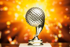 Golf ball trophy against shiny background Stock Photos