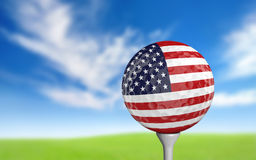 Golf ball with United States flag colors sitting on a tee Stock Image