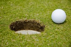 Golf ball very close to a hole Royalty Free Stock Photos