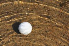 Golf Ball in a Water Hazard. Golf Ball on Sandy Bottom of a Water Hazard royalty free stock photo