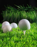 Golf ball on white tee with green grass field Stock Photography