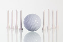 Golf ball and white  tees on the glass table Royalty Free Stock Images