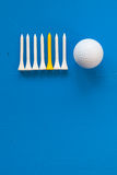 Golf ball and wooden golf tees on the blue desk Stock Images