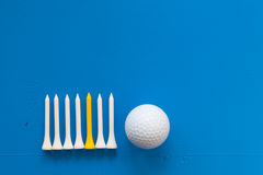 Golf ball and wooden golf tees on the blue desk Stock Photos