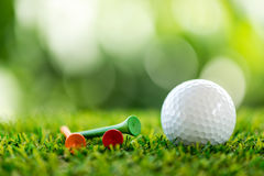Golf ball and wooden tee Royalty Free Stock Photography