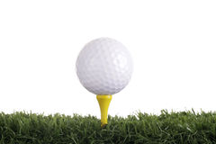 Golf ball with yellow tee. Golf ball on a yellow tee on white background and grass foreground Stock Image