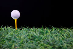 Golf ball on yellow tee Stock Images