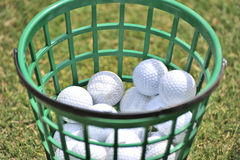 Golf Balls. Many golf balls kept in a green basket Stock Image