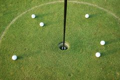 Golf balls. Group of golf balls around the hole taken from above Royalty Free Stock Photos