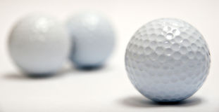 Golf Balls. An in focus blank golf in-front of two blurred golf balls royalty free stock photography