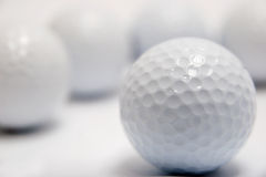 Golf Balls. An in focus blank golf in-front of four blurred golf balls Royalty Free Stock Image
