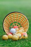 Golf balls. Pouring out of basket onto grass Royalty Free Stock Photography