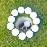 Golf balls around hole with ball in the cup Stock Photography