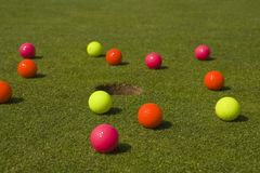 Golf balls around a hole in a golf course Stock Photo