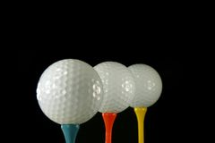 Golf Balls on Black. Three Golf Balls, second is in focus, black background stock image