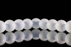 Golf balls on the black glass desk Stock Photography