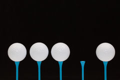 Golf balls on blue  tees Stock Images
