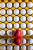 Golf balls in box for eggs and red heart. Golf balls in paper carton for eggs and love symbol on a glass desk Stock Photography
