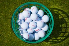 Golf balls bucket. A bucket of golf balls at the driving range stock images