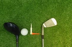 Golf balls and golf clubs on green grass royalty free stock image