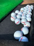 Golf balls on driving range ready to hit off royalty free stock photography