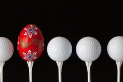 Golf balls and egg on a black glass desk Stock Images