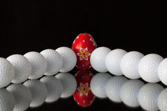Golf balls and egg on a black glass desk Royalty Free Stock Photography