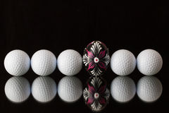 Golf balls and egg on a black glass table Stock Images