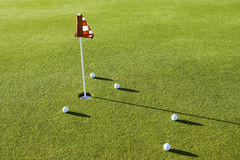 Golf Balls By Flag On Course Stock Photo