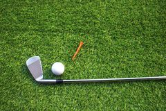 Golf balls and golf clubs on green grass stock image
