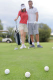 Golf balls on green with golfing couple in background Stock Image