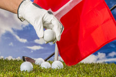 Golf balls, green grass, clouds background Stock Image