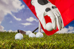 Golf balls, green grass, clouds background Royalty Free Stock Photography