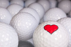 Golf balls with love symbol. On the black glass table stock images