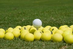 Golf Balls (Medaphore). Yellow Golf Ball at at driving range. White ball set on tee above the rest Stock Photos