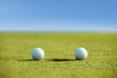 Golf balls near hole Stock Image
