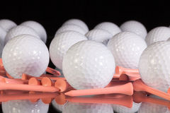 Golf balls and pink tees on the black glass table Royalty Free Stock Photography