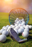 Golf balls. Pouring out of basket onto grass stock photos