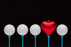 Golf balls and red heart on wooden tees Stock Photo