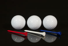 Golf Balls Red White Blue Tees. Three white golf balls with three tees one red, one white and one blue on black reflective surface Stock Images