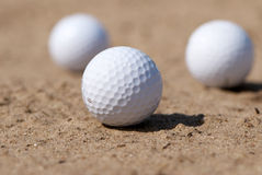 Golf balls On sand Stock Photography