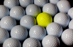 Golf balls. Single yellow ball mixed within many white balls. Royalty Free Stock Images