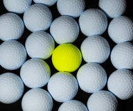 Golf balls. Single yellow ball mixed within many white balls. Royalty Free Stock Image