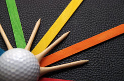 Golf Balls and Tees. A colorful display of a golfing equipment isolated on a black leathery background Royalty Free Stock Image