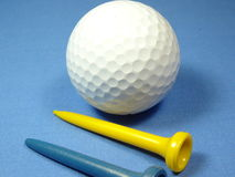 A Golf balls. A golf  balls and tees on blue background Stock Images