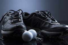 Golf balls, tees and shoes  on dark blue background. Golf equipment consisting of balls, tees and shoes,  on dark blue background Stock Photo
