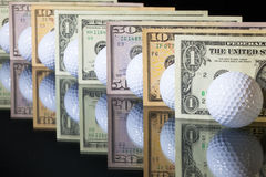 Golf balls and US dollars banknotes Stock Images