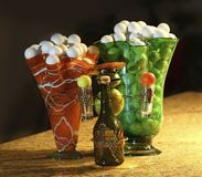 Golf Balls In Vase. Collected golf balls presented in colorful vases. Tequila shooter holder with Mexican frog.  Metal art and glass Royalty Free Stock Images