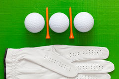 Golf balls and wooden golf tees on the green table Royalty Free Stock Photo