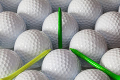 Golf balls and wooden tees in open box. White golf balls and  different wooden tees Royalty Free Stock Image